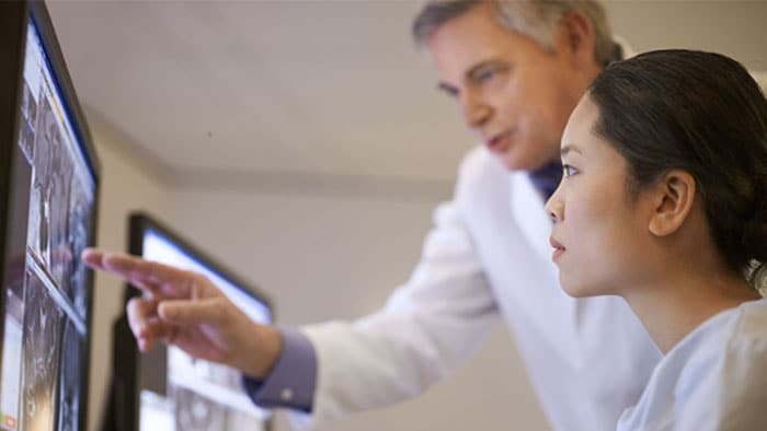 Clinicians analyzing patient data in using  advanced imaging visualization